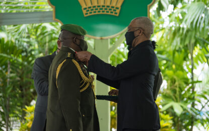 Pres Granger presents Brig. Godfrey Bess with Instruments of Commission